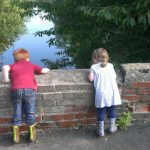 Ben and Chloe playing pooh-sticks on a low bridge