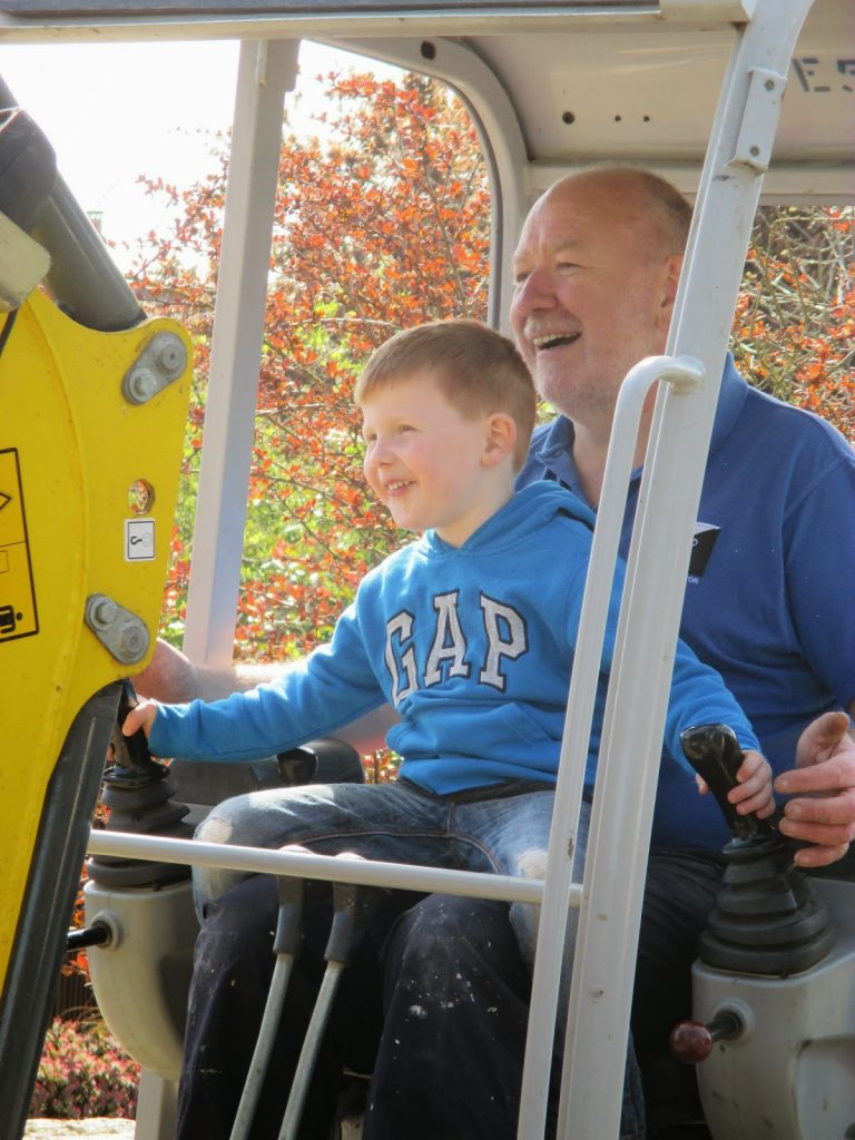 Little boy ridding a digger with his Grandad