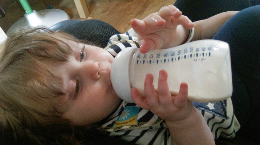 little girl learning to drink from her bottle - breast to bottle