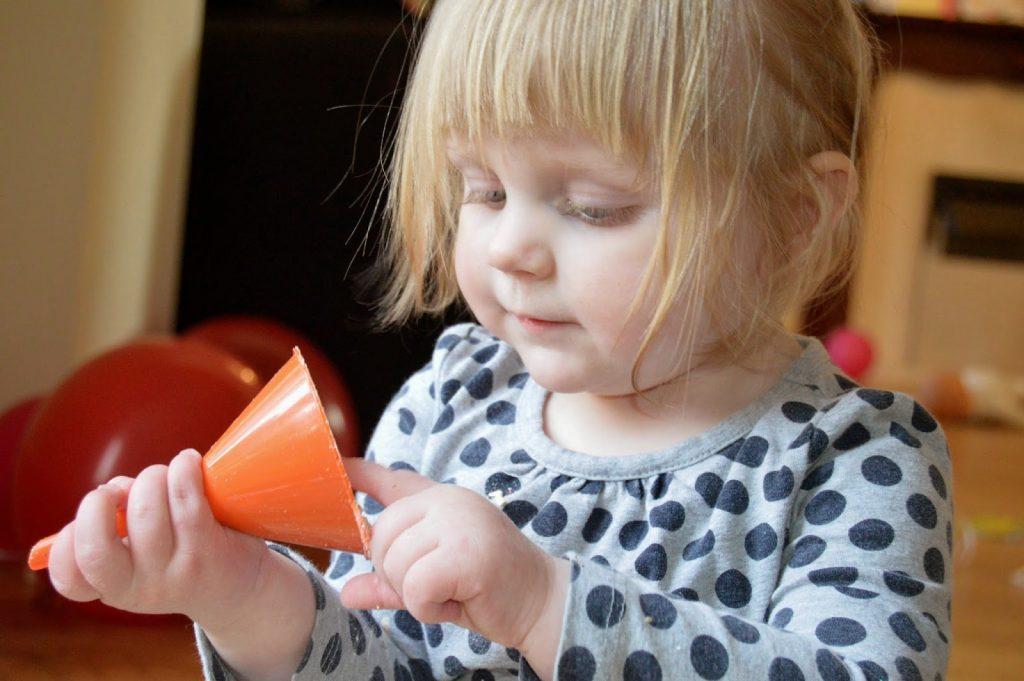 toddler investigating funnel