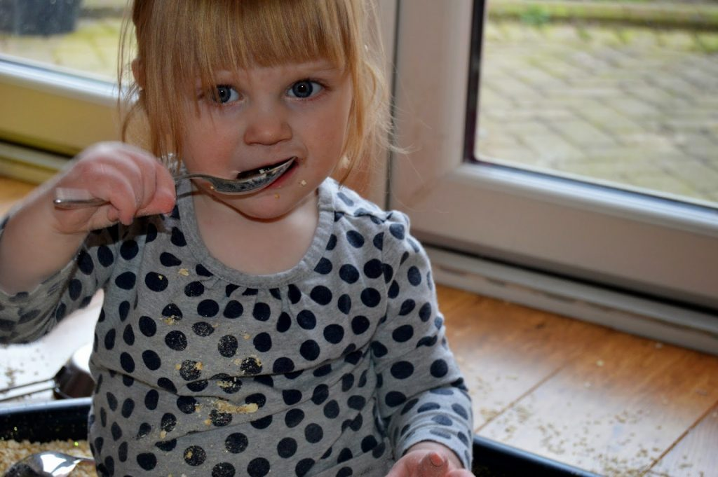 toddler with big spoon in mouth