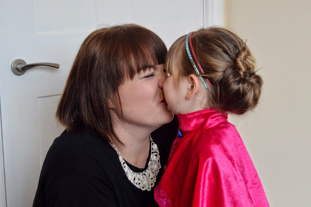 Mummy kissing daughter dressed in Frozen costume