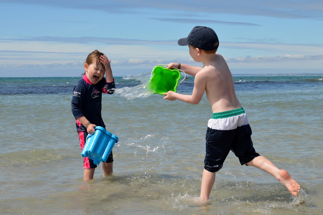 Little boy throwing a bucket of seawater in his little sister's face