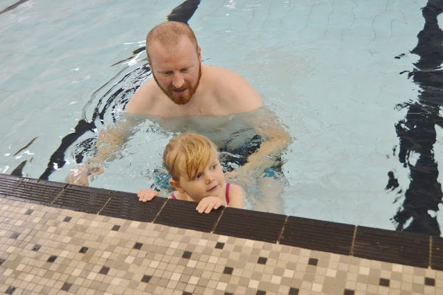 "Little girl learning to ""monkey walk"" on the wall in her Puddle Ducks swimming lesson"