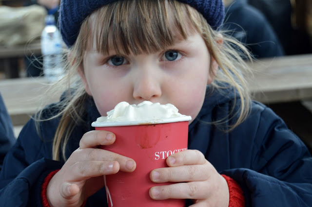 Little girl warming her hands on a hot chocolate with whipped cream at Stockeld Park Christmas Adventure