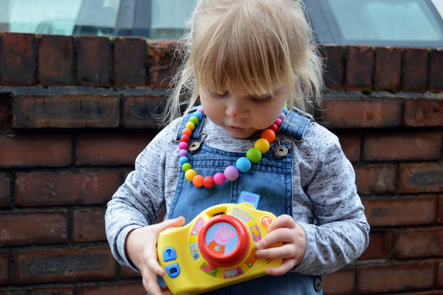 Toddler with Peppa Pig toy camera