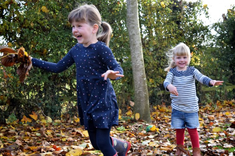 Amy & Chloe throwing autumn leaves in the garden