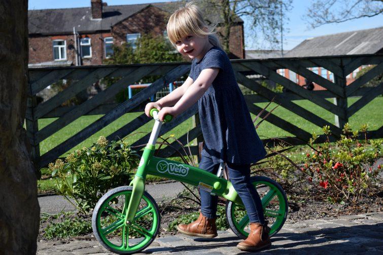 little girl riding green Y Velo Balance Bike