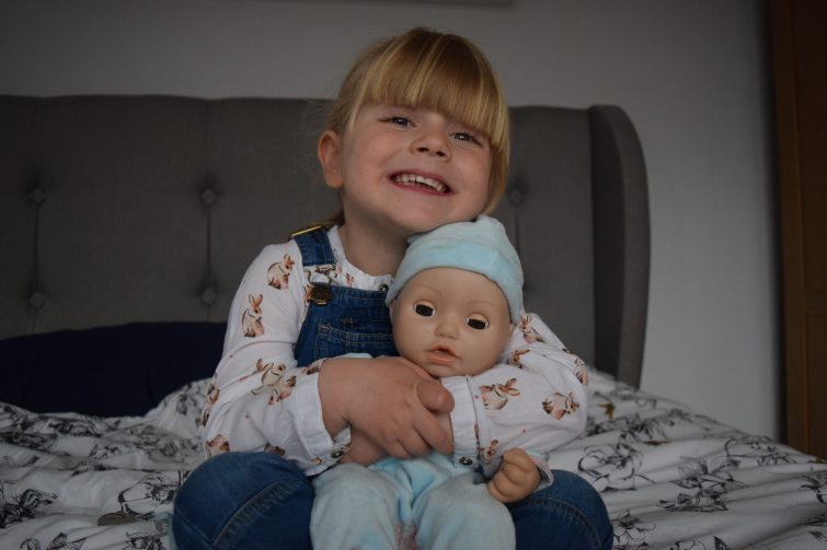 Little girl with Baby Annabell's brother