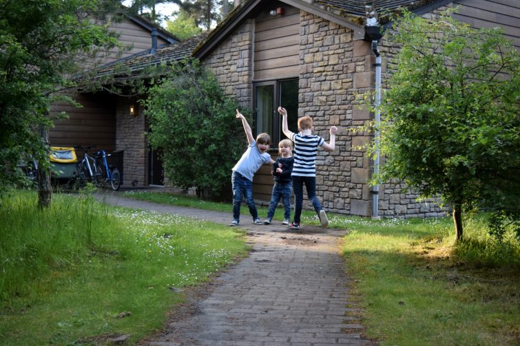 Children playing outside an executive lodge at Center Parcs Whinfell Forest