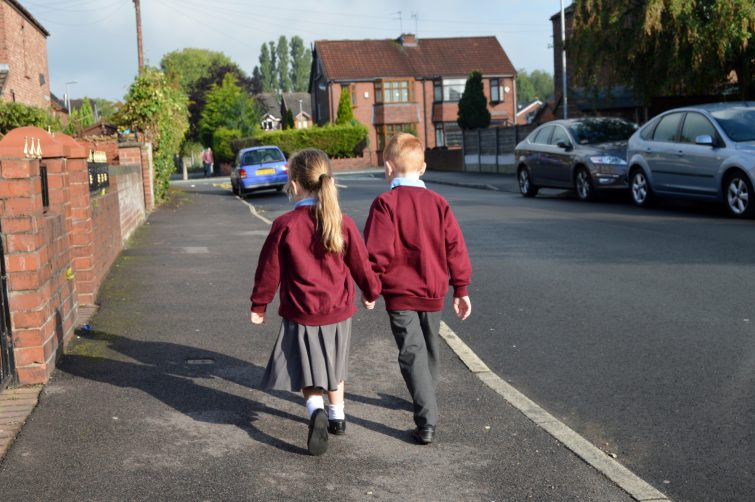 brother and sister walking to school in September - back to school