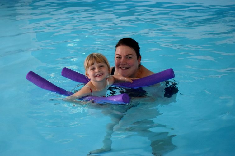 Toddler swimming with woggles in her Puddle Ducks lesson