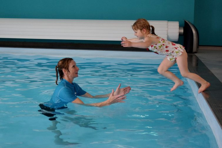 Little girl jumping into the pool to her swimming teacher