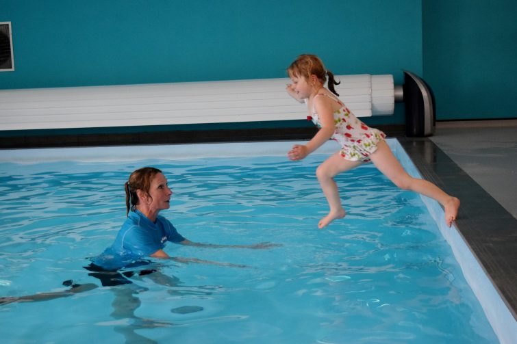 Little girl leaping into the swimming pool