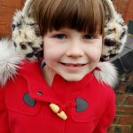 Little girl wearing leopard print ear muffs and a red duffle coat with fur trim hood