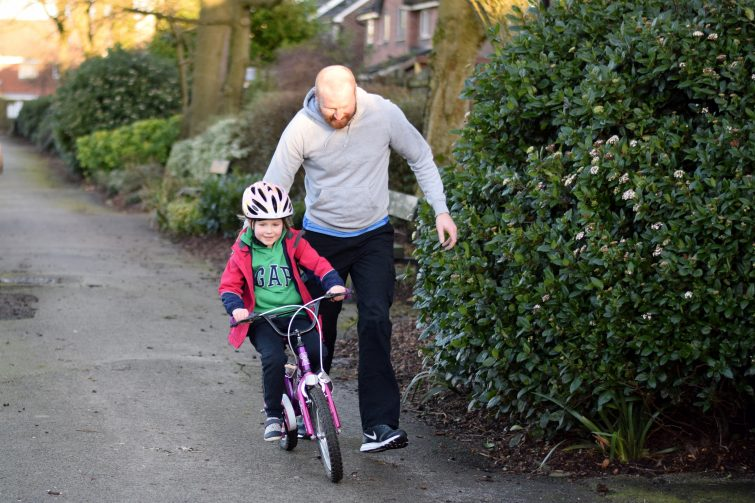Daddy teaching his little girl how to ride her bike