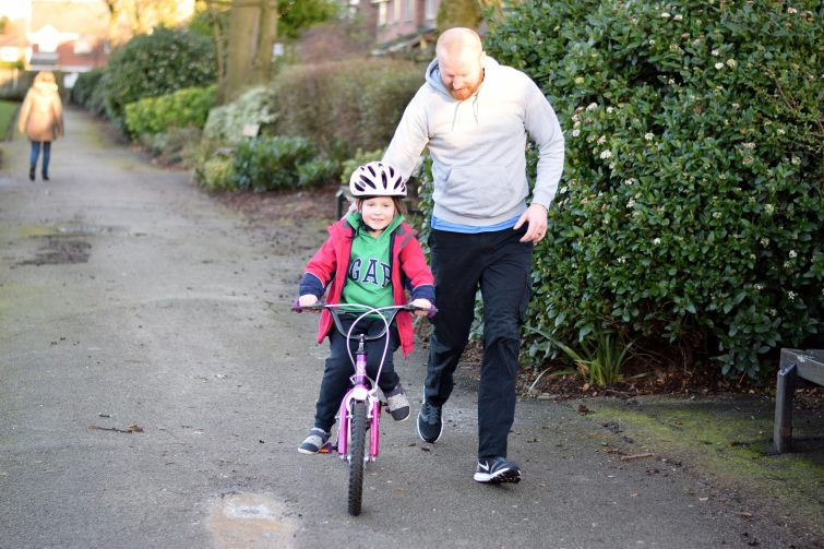 Little girl learning to ride a bike with Daddy running alongside her