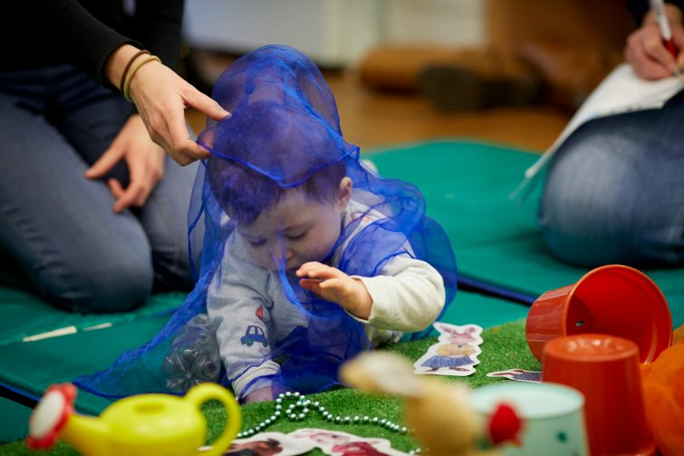 Twinkleboost story and sensory activities - baby playing with net scarf