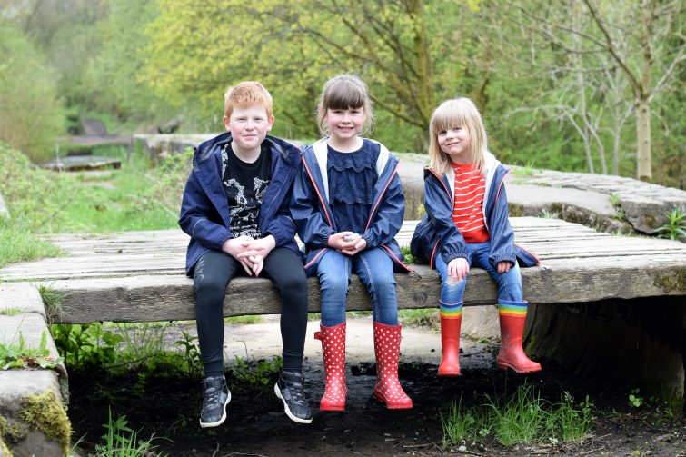 Three siblings sitting on a wooden bench over a disused canal