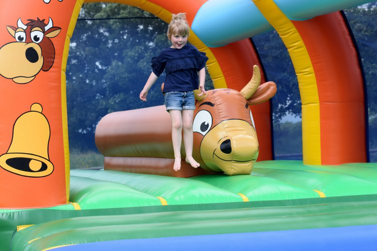 Little girl jumping on bouncy castle at Chateau de Lez Eaux campsite