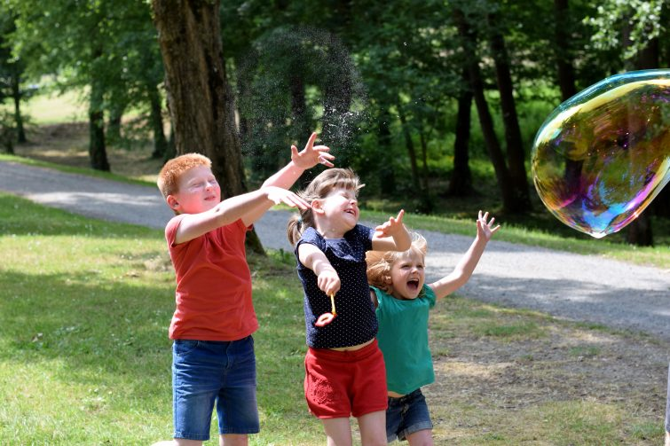 Children popping enormous bubbles