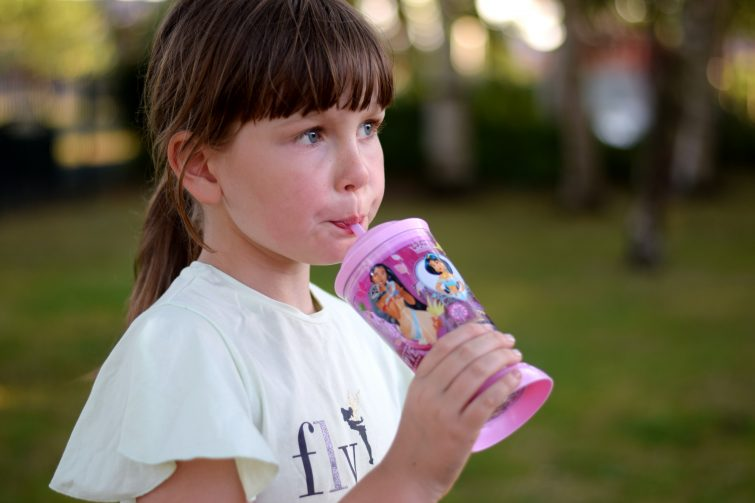Girl drinking from Disney store princess straw cup