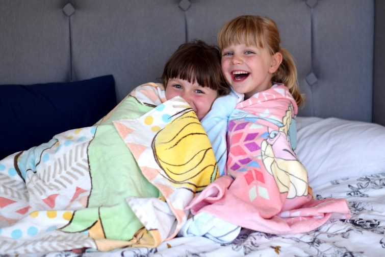 Girls snuggled up in their Disney store beach towels ready for bed