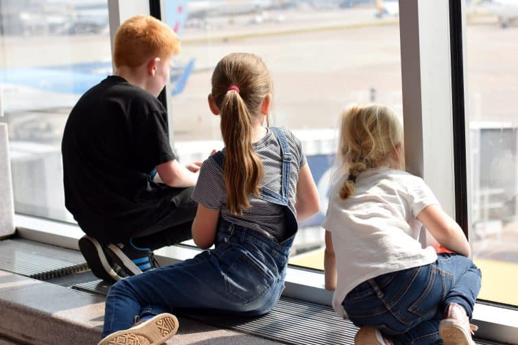 Kids watching planes out of the window at Manchester Airport
