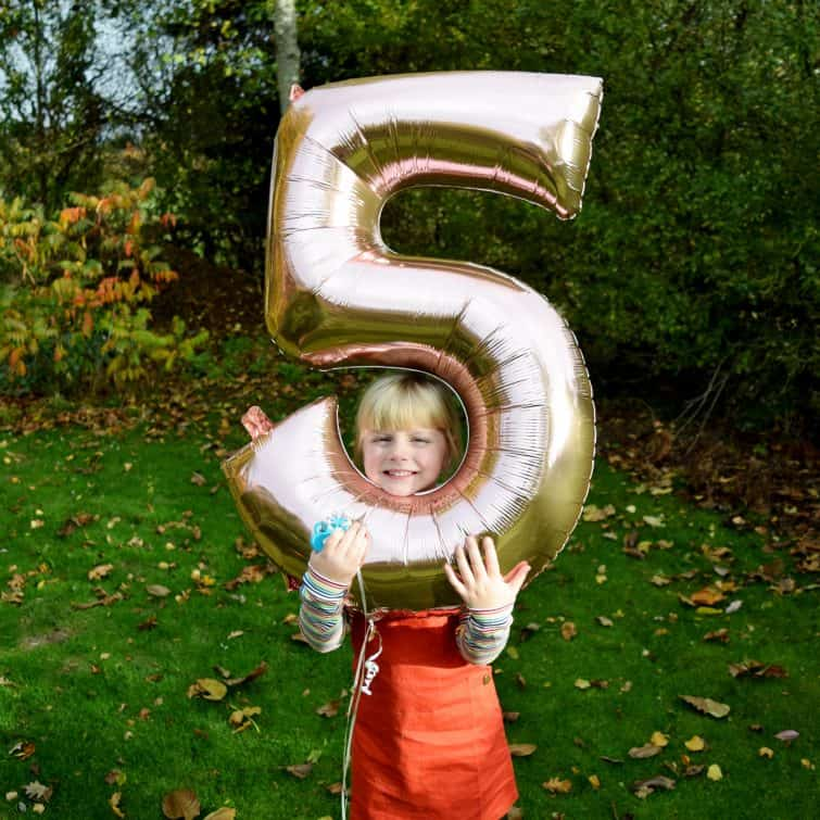 Cheeky little girl with her head in a fifth birthday balloon