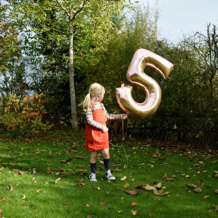 Little girl with helium balloon on 5th birthday