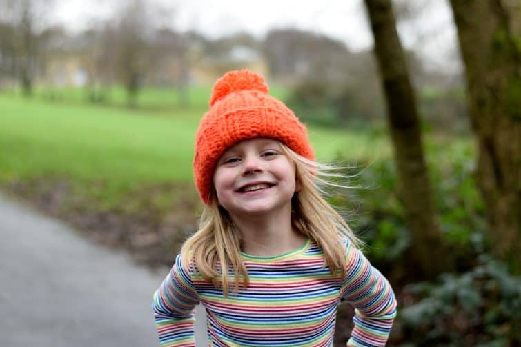 cheeky little girl in orange bobble hat