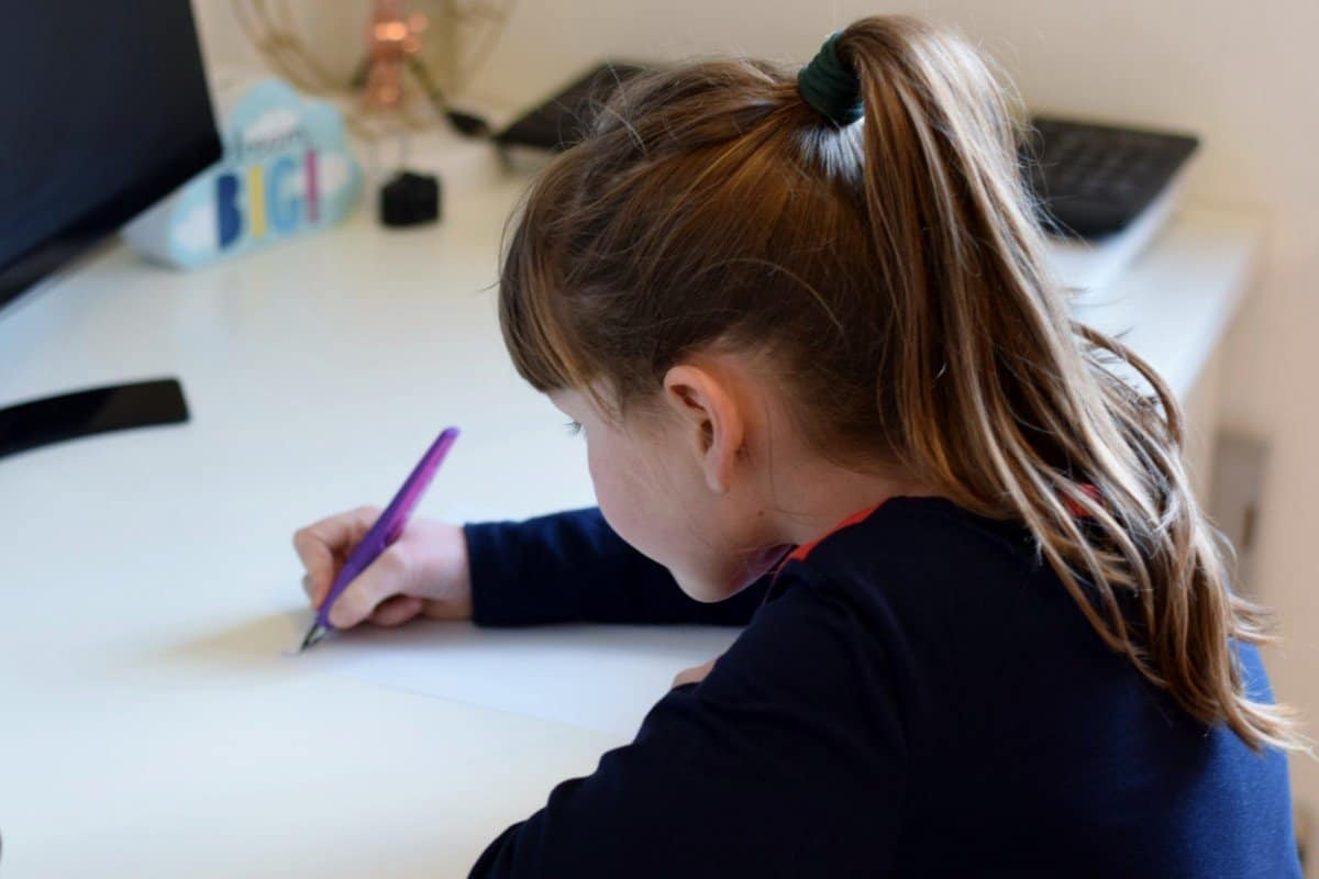 Little girl writing with Stabilo fountain pen