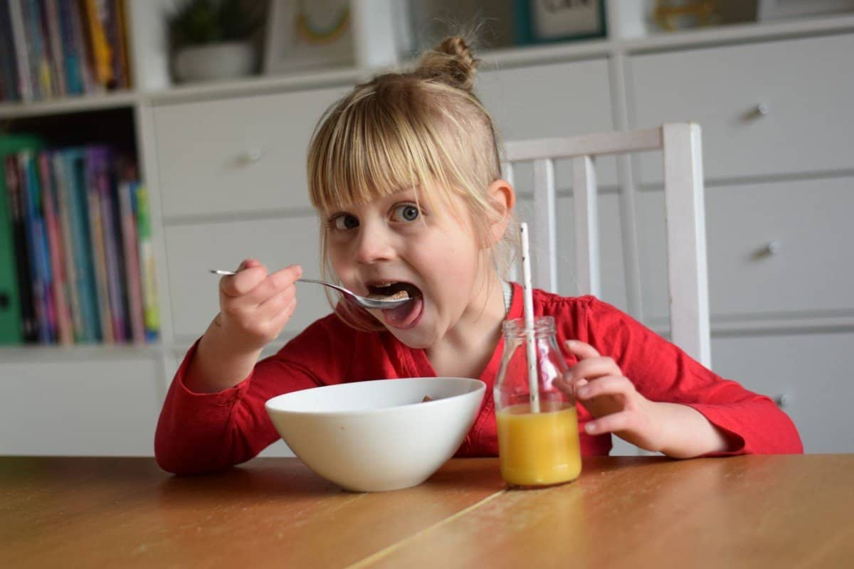 little girl eating breakfast cereal with orange juice