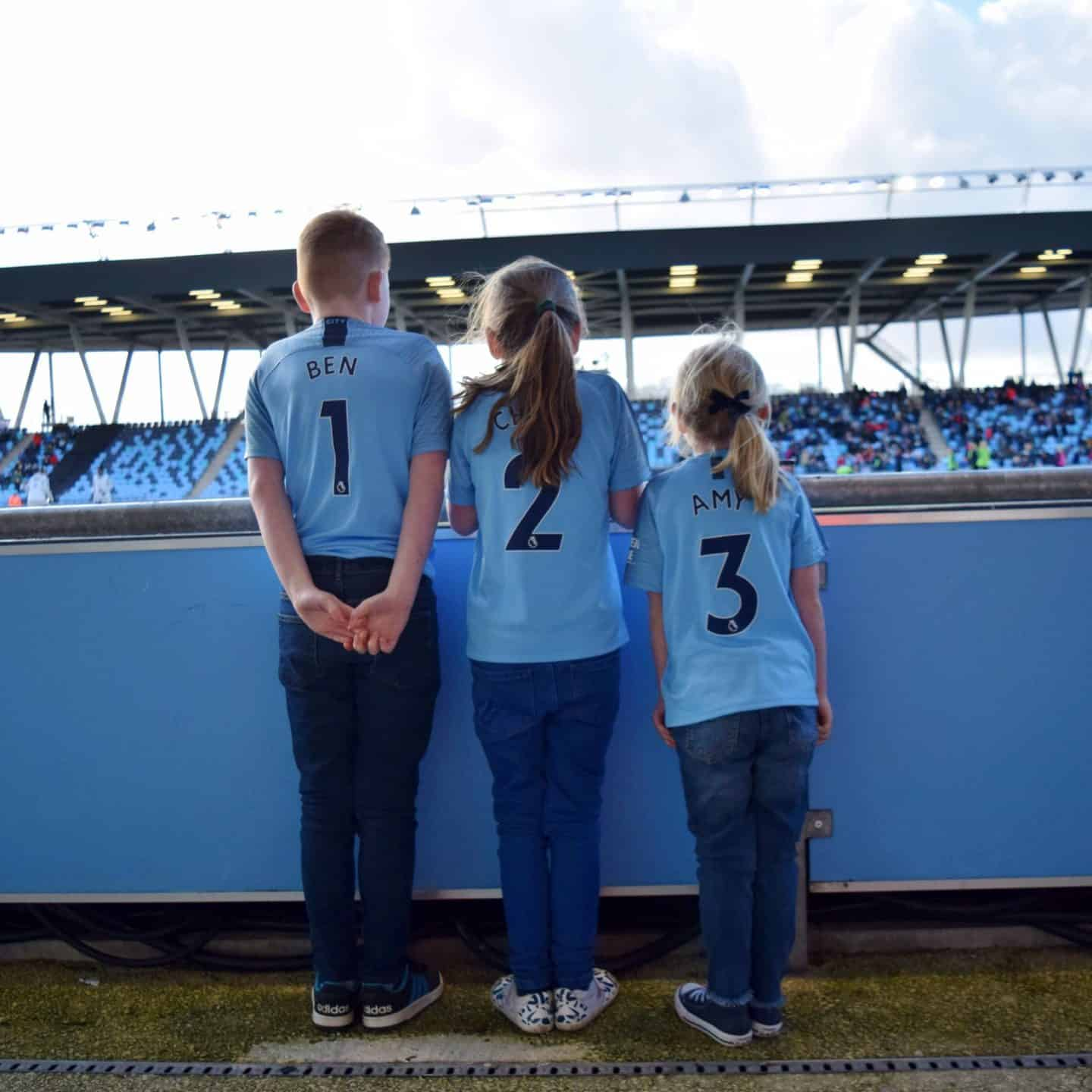 Siblings wearing Manchester City shirts.