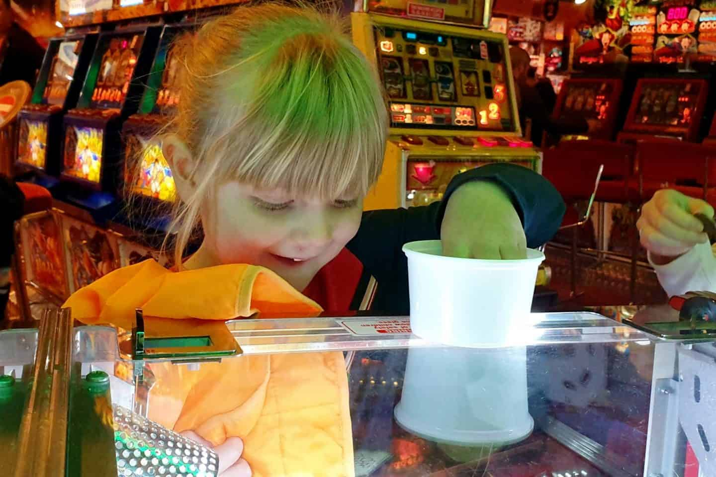 Little girl playing the 2p machines at arcades in Blackpool