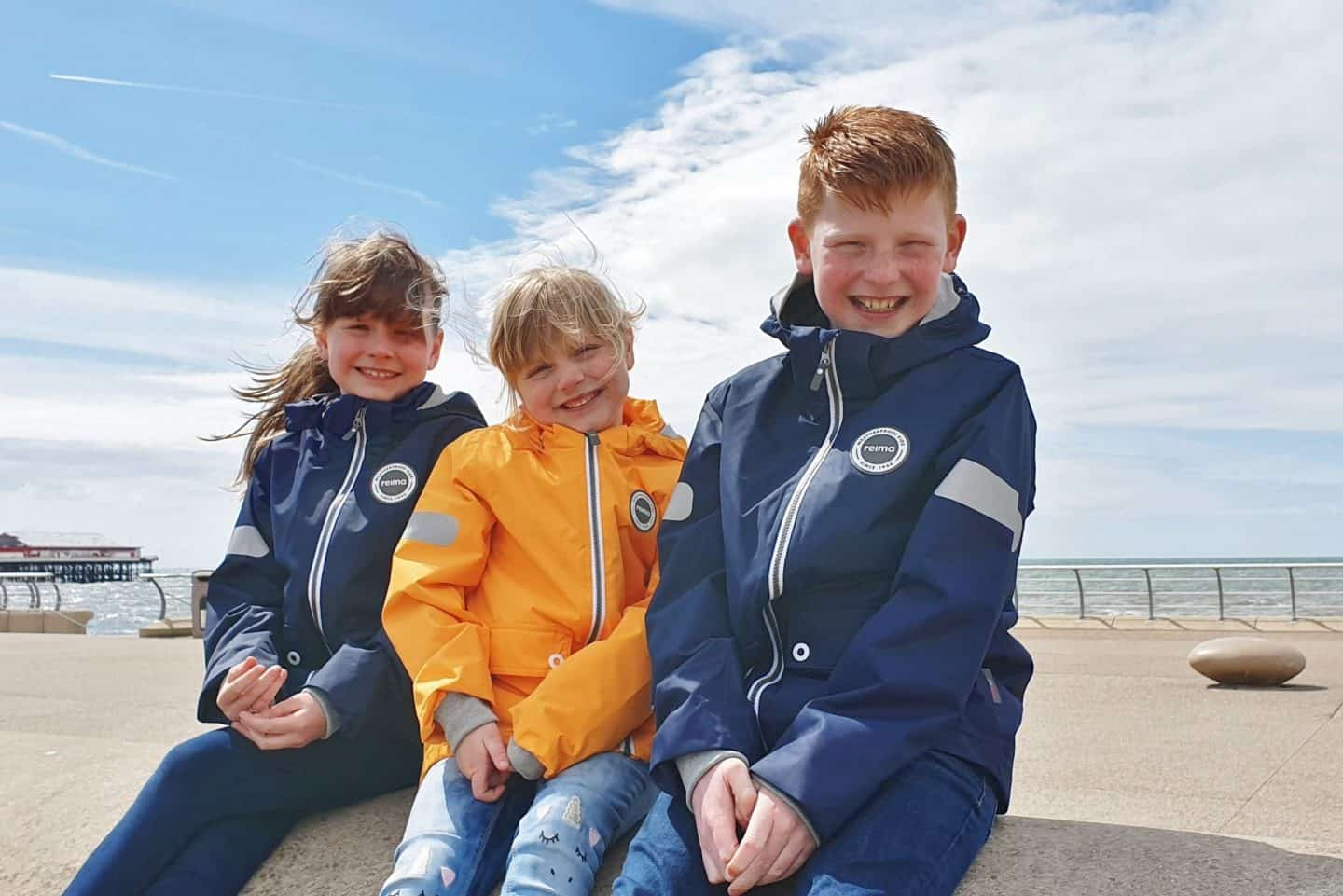 kids at seaside wearing reimatec waterproof jacket