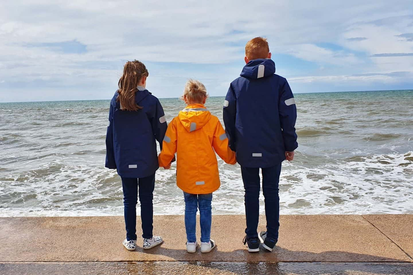 children standing on the beach showing off the reflective detailing on their reima waterpoof jackets
