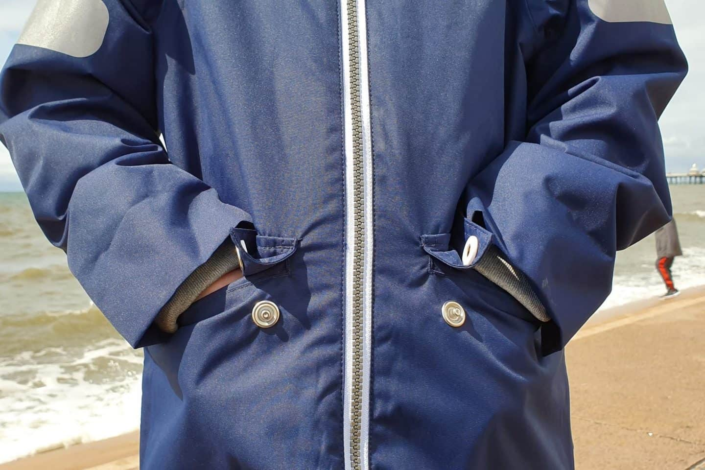 Hands in pockets showing White detailing on the Reimatec jacket.