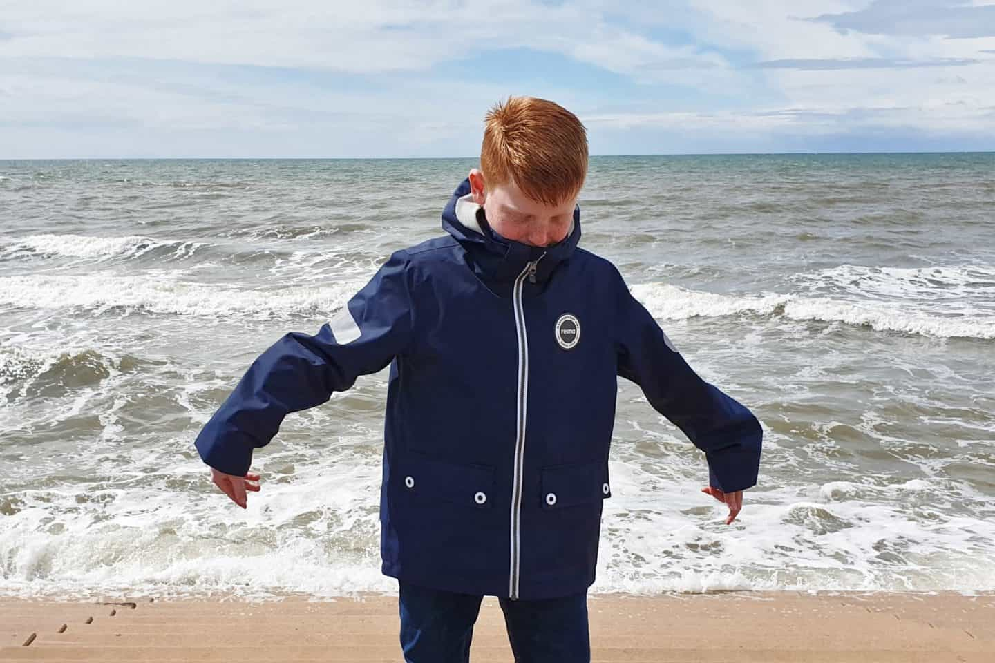 Boy dancing on the sea front wearing navy waterproof jacket with white detailing