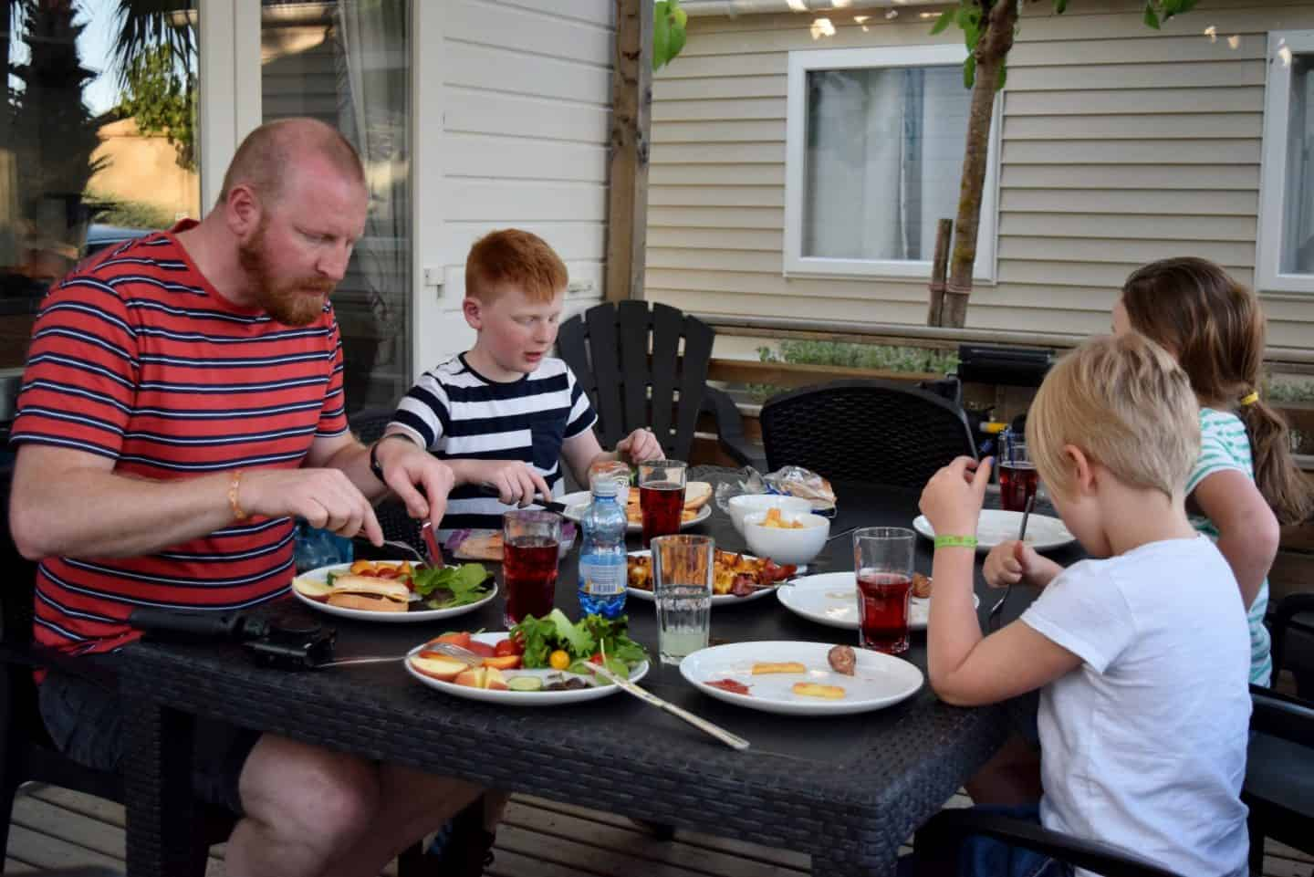 Family eating lunch on the deck of a Eurocamp Avant holiday home