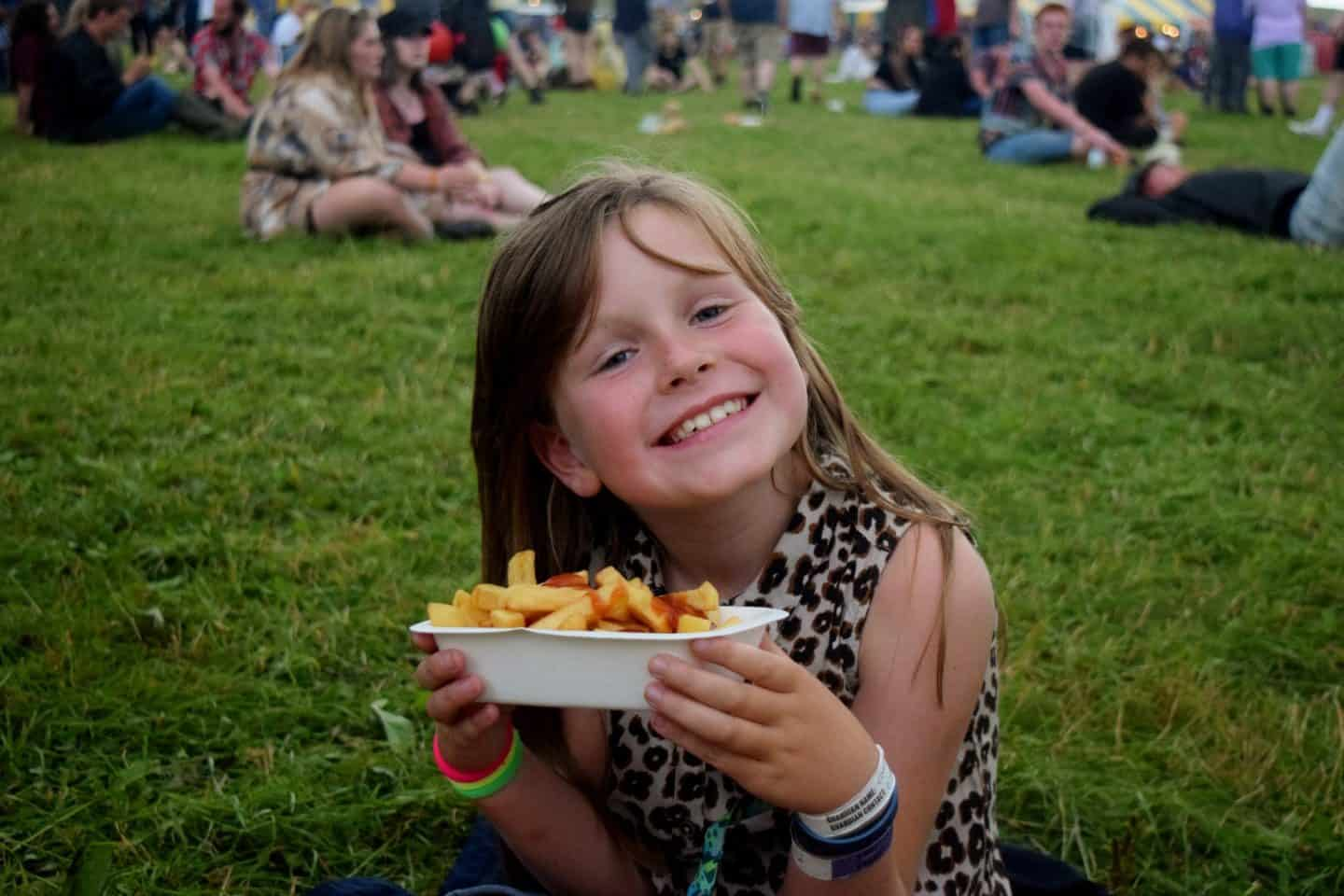 Little girl eating expensive chips at a festival