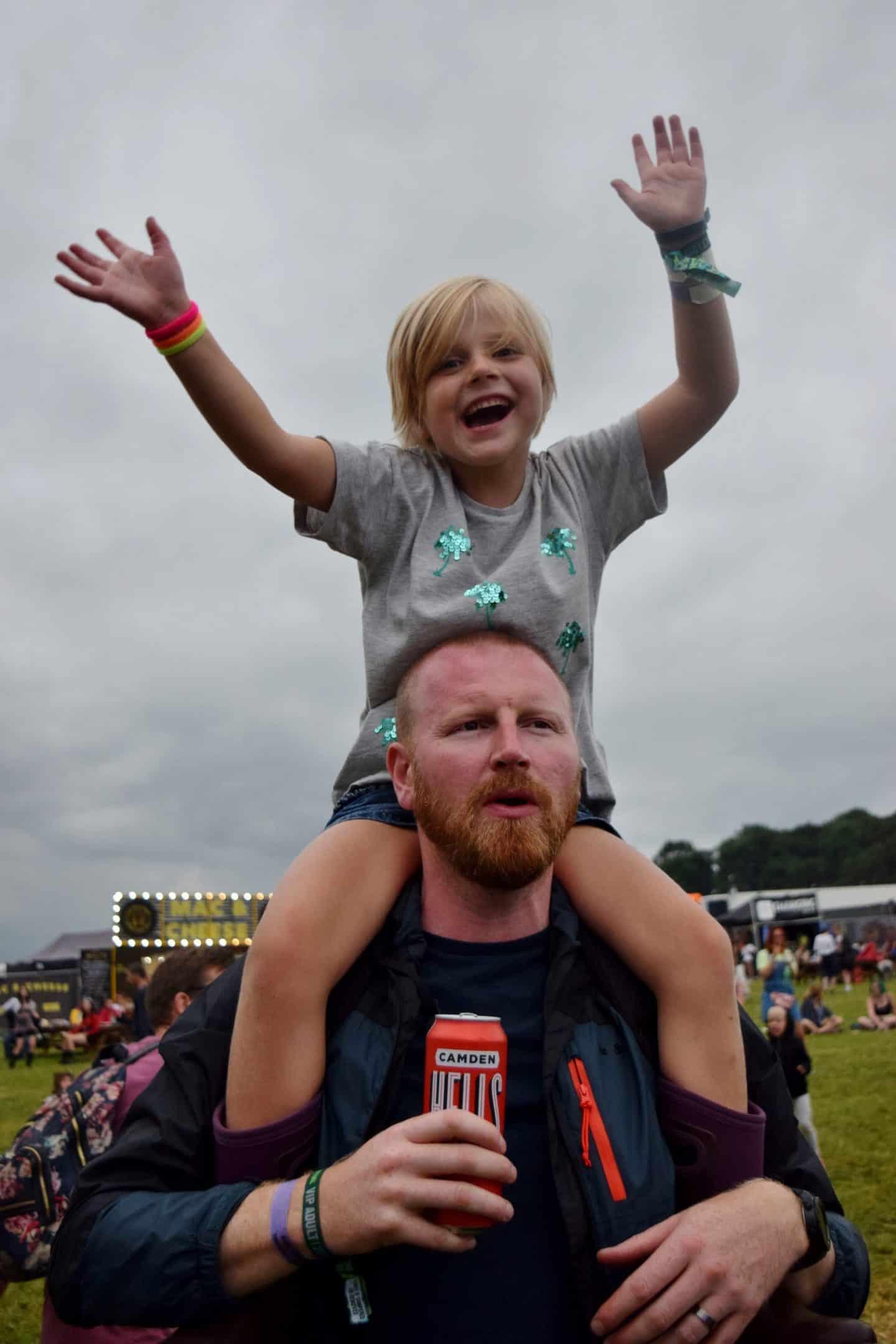 Little girl sat on her Dad's shoulders at a festival