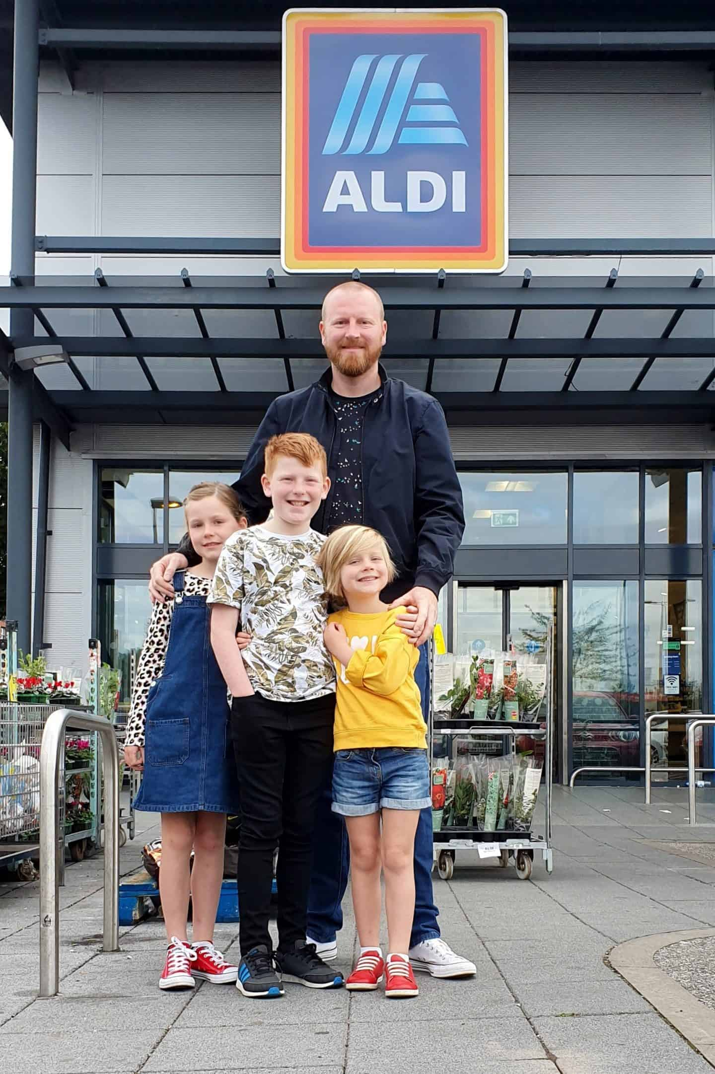 Dad and children stood outside Aldi ready to do the weekly shop and collect Kit for Schools stickers