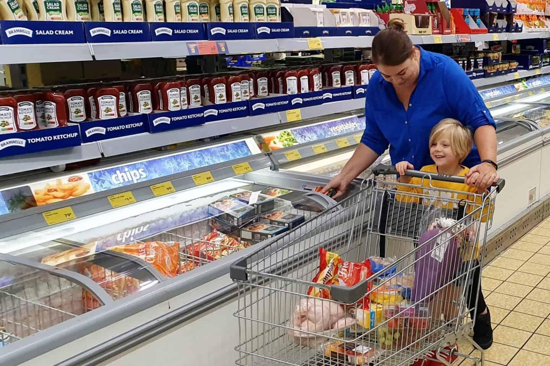 Mum shopping with little girl in Aldi - pushing shopping trolley
