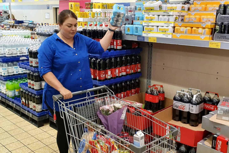 Mum shopping in Aldi - putting groceries in trolley