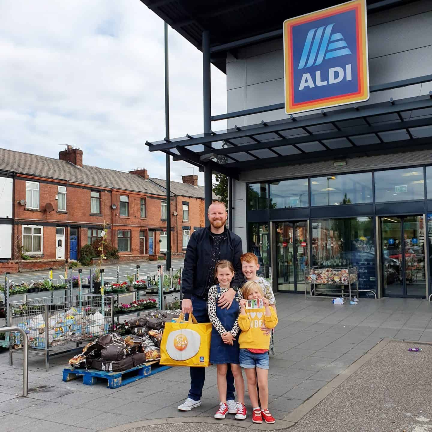 Dad and children outside ALDI with shopping bag