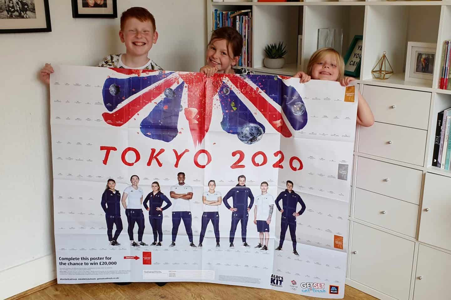 Children showing off the Aldi Kit for Schools poster - schools need to collect stickers and add to this poster to earn a Mini Olymics Kit
