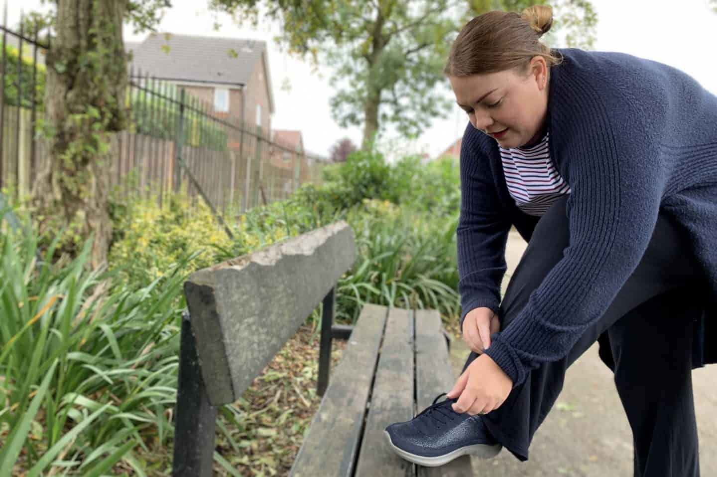 Fastening shoe laces on park bench